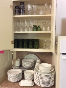Beautiful white dishes with stylish stemware and green glassware.